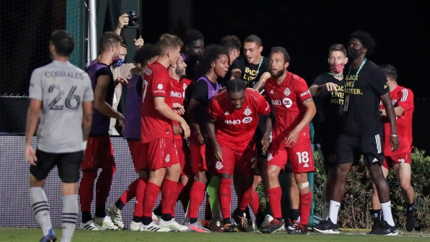 Toronto FC forward Ayo Akinola, centre, celebrates with teammates after scoring his third goal of the game during second half MLS soccer action against the Montreal Impact, in Kissimmee, Fla., Thursday, July 16, 2020. (THE CANADIAN PRESS / AP-John Raoux)