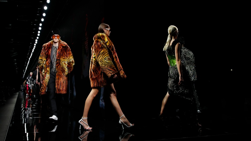 In this Friday, Feb. 21, 2020 file photo, models wear creations as part of Versace Fall/Winter 2020/2021 collection, presented in Milan, Italy. Giorgio Armani, Fendi, Prada and Versace are all returning to the runway in September, according to the Milan Fashion Week calendar published on Wednesday, Aug. 12, 2020. After the coronavirus pushed many fashion houses to make on-line only presentations during the last fashion week in July, more than half of participating Milan fashion houses will hold physical shows to present previews for Spring-Summer 2021 in September. (AP Photo/Antonio Calanni, File)