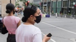 People wear face masks as they wait to cross a street in Montreal, Sunday, August 9, 2020, as the COVID-19 pandemic continues in Canada and around the world. THE CANADIAN PRESS/Graham Hughes