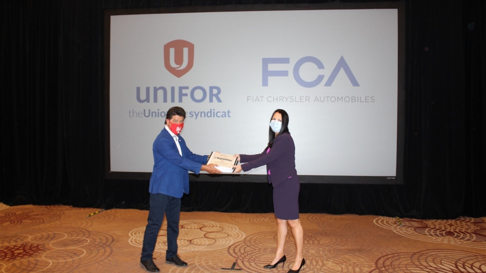 FCA Canada head of human resources Jacqueline Olivia and Unifor National president Jerry Dias kick-off talks with document exchange at the Sheraton Centre in Toronto, Ont.