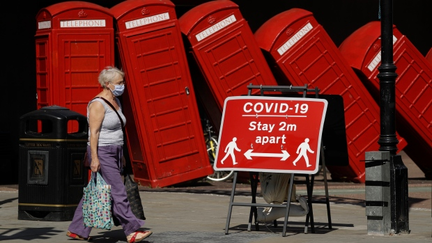 """In this file photo dated Monday, June 22, 2020, a sign requesting people stay two metres apart to try to reduce the spread of COVID-19 is displayed in front of """"Out of Order"""" a 1989 red phone box sculpture by British artist David Mach, in London. (AP Photo/Matt Dunham, FILE)"""