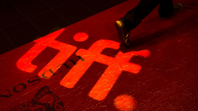 A man walks on a red carpet displaying a sign for the Toronto International Film Festival at the TIFF Bell Lightbox in Toronto on Wednesday, September 3, 2014. THE CANADIAN PRESS/Darren Calabrese