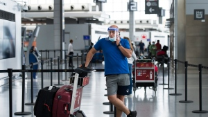 A man wearing a mask and full face shield talk on the phone at Toronto's Pearson International Airport on June 23, 2020. THE CANADIAN PRESS/Nathan Denette