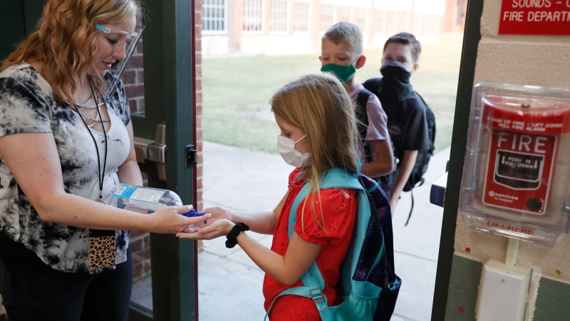 FILE - In this Aug. 5, 2020, file photo, wearing masks to prevent the spread of COVID19, elementary school students use hand sanitizer before entering school for classes in Godley, Texas. (AP Photo/LM Otero, File)