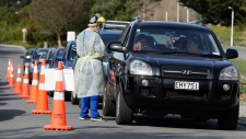 Medical staff prepare take a COVID-19 test from a visitor to a drive through community based assessment centre in Christchurch, New Zealand, Thursday, Aug. 13, 2020. (AP Photo/Mark Baker)