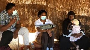 Dr. Idriss Abdallah of the health activism group called Banlieues Sante, left, nurse Caroline Andoum, center, talk inside a tent in Bondy, north of Paris, Thursday Aug. 6, 2020. (AP Photo/Arno Pedram)