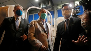 Hong Kong media tycoon and newspaper founder Jimmy Lai, center, walks out from a police station after being bailed out in Hong Kong, Wednesday, Aug. 12, 2020. (AP Photo/Kin Cheung)