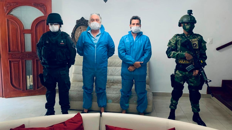 In this photo released by Colombia's Prosecutor's Press Office, a police officer and a soldier flank Mark Grennon, second left, and his son Joseph Grennon, during a raid in Santa Marta, Colombia, Tuesday, Aug. 11, 2020. (Colombia's Prosecutor's Press Office via AP)