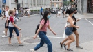 People wear face masks as they cross a street in Montreal, Sunday, August 9, 2020, as the COVID-19 pandemic continues in Canada and around the world. THE CANADIAN PRESS/Graham Hughes