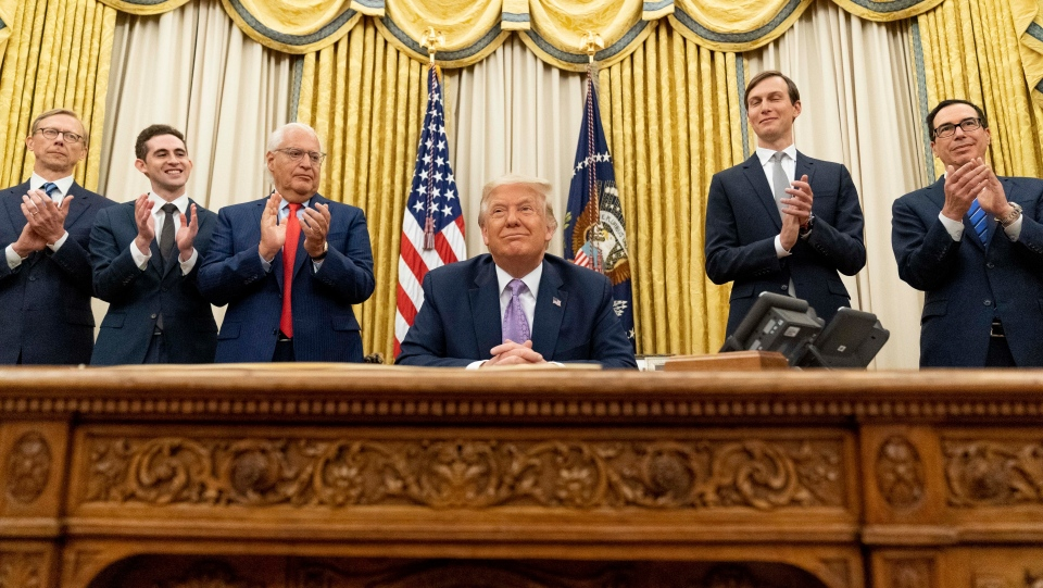 U.S. President Donald Trump, accompanied by F=from left, U.S. special envoy for Iran Brian Hook, Avraham Berkowitz, Assistant to the President and Special Representative for International Negotiations, U.S. Ambassador to Israel David Friedman, President Donald Trump's White House senior adviser Jared Kushner, and Treasury Secretary Steven Mnuchin, applaud in the Oval Office at the White House, Wednesday, Aug. 12, 2020, in Washington. (AP Photo/Andrew Harnik)