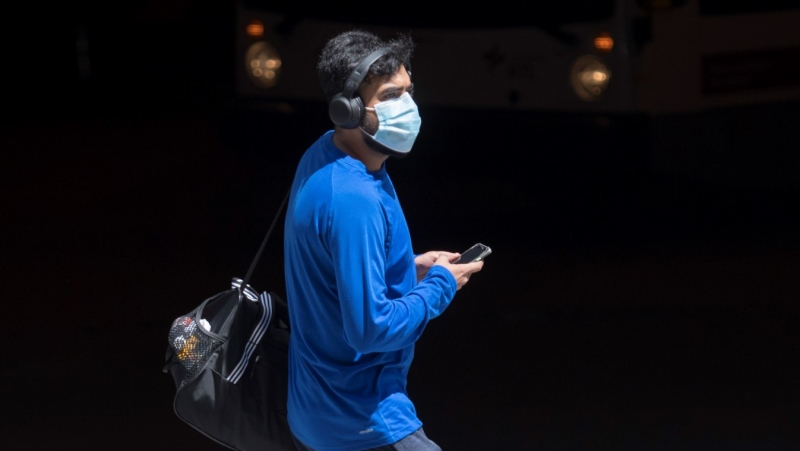 A man wears a face mask as he walks along a street Saturday, Aug. 8, 2020, as the COVID-19 pandemic continues in Canada and around the world. THE CANADIAN PRESS/Graham Hughes​