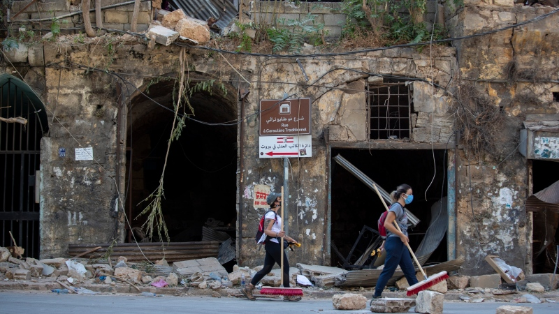 Women with brooms pass by a historic building damaged by Tuesday's explosion in the Gemmayzeh neighborhood, Beirut, Lebanon, Saturday, Aug. 8, 2020. (AP Photo/Hassan Ammar)