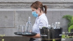 A server wears a face mask as she carries a tray of glasses and water at a restaurant in Montreal, Sunday, July 5, 2020. THE CANADIAN PRESS/Graham Hughes
