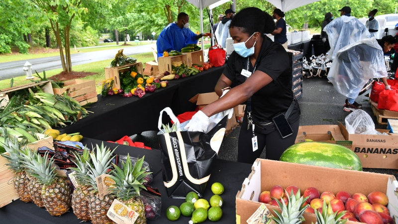 A volunteer prepares a food package during Goodr Pop-Up Grocery Store Shopping Experience at Lucky Shoals Park on May 0, 2020 in Norcross, Geo. (Paras Griffin/Getty Images/CNN)