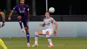 Orlando City's Tesho Akindele passes against Montreal Impact defender Luis Binks, right, during the first half of an MLS soccer match, Saturday, July 25, 2020, in Kissimmee, Fla. (AP Photo/John Raoux)