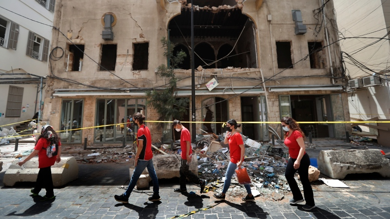 University students who volunteered to help clean damaged homes and give other assistance, pass in front of a building that was damaged by last week's explosion, in Beirut, Lebanon, Tuesday, Aug. 11, 2020. (AP Photo/Hussein Malla)