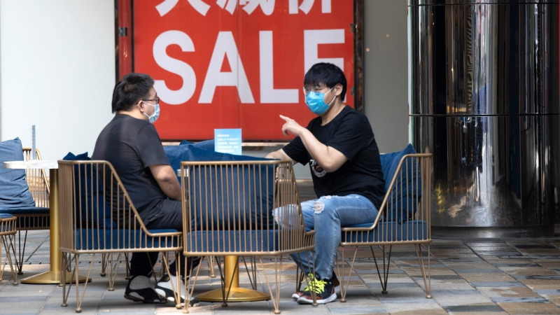 Shoppers wearing mask to curb the spread of the coronavirus visit a retail district in Beijing on July 22, 2020. (AP Photo/Ng Han Guan)