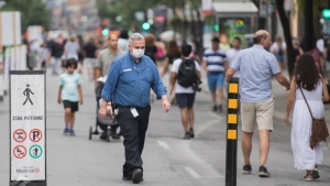 People wear face masks as they walk along a pedestrian zone on Sainte-Catherine Street in Montreal, Sunday, August 9, 2020, as the COVID-19 pandemic continues in Canada and around the world. THE CANADIAN PRESS/Graham Hughes