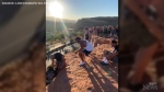 Caught on cam:  A university football team helps to rescue a woman dangling from a cliff after her hair got caught in her equipment