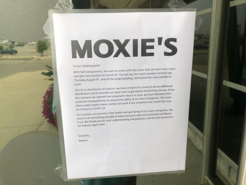 A sign posted outside a Winnipeg Moxie's restaurant after an employee tested positive for COVID-19. Source: Ken Gabel.