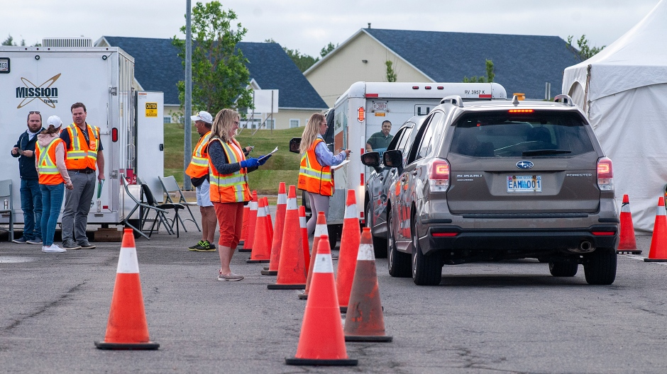 Volunteers examine the documents of motorists who just came off the Confederation Bridge in Borden-Carleton, P.E.I., Friday, July 3, 2020. (THE CANADIAN PRESS/Brian McInnis)