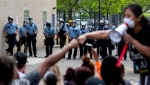 In this May 27, 2020, file photo, people gather in front of the Minneapolis police standing guard, as they protest the arrest and death of George Floyd. (Carlos Gonzalez/Star Tribune via AP, File)