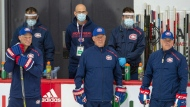 Montreal Canadiens head coach Claude Julien, centre, flanked by assistant coaches Kirk Muller, left, and Domenic Ducharme, right, keep an eye on practice as support staff wearing protective equipment look on as they hold their first team practice Monday, July 13, 2020 in Brossard, Que. THE CANADIAN PRESS/Ryan Remiorz