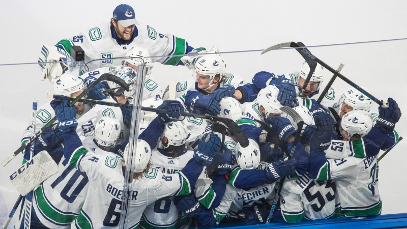 Vancouver Canucks players celebrate the win over the St. Louis Blues during overtime in first round NHL Stanley Cup playoff hockey series in Edmonton, on Friday August 14, 2020. THE CANADIAN PRESS/Jason Franson