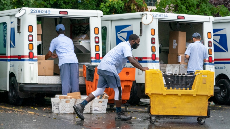 Letter carriers load mail trucks for deliveries at a U.S. Postal Service facility in McLean, Va. The success of the 2020 presidential election could come down to a most unlikely government agency: the U.S. Postal Service. (AP Photo/J. Scott Applewhite)