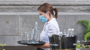 People wear protective gear as they take orders at a restaurant in Montreal, Sunday, July 19, 2020. As the Canadian economy continues to adapts to the reality of the COVID-19 pandemic, some restaurants in the country's most populous city are saying goodbye to a service industry staple: tipping. THE CANADIAN PRESS/Graham Hughes