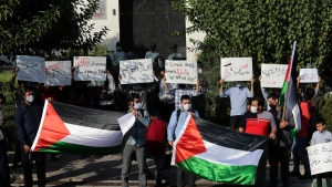 A group of protesters hold placards against Israel and United Arab Emirates and in support the Palestinians while holding Palestinian flags during a gathering outside the United Arab Emirates' embassy in Tehran, Saturday, Aug. 15, 2020, to condemn the UAE's historic deal with Israel to open up diplomatic relations. (AP Photo/Ebrahim Noroozi)