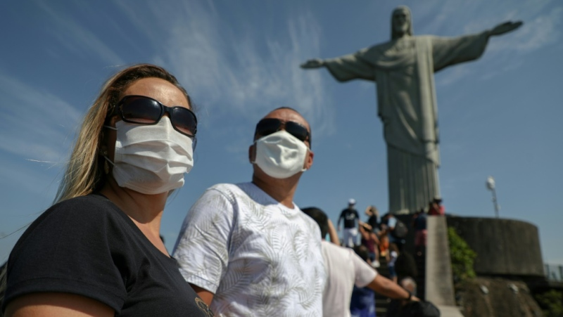 Tourists wearing face masks against the coronavirus enjoy the view from the base of Rio de Janeiro's iconic Christ the Redeemer statue on August 15, 2020 as the city reopened some tourist attractions closed months ago. (AFP)