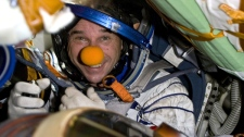 Canadian space tourist Guy Laliberte smiles while sitting inside the Soyuz spacecraft, shortly after landing near Arkalyk, Kazakhstan, on Sunday, Oct. 11, 2009. (AP / Sergei Remezov, Pool)