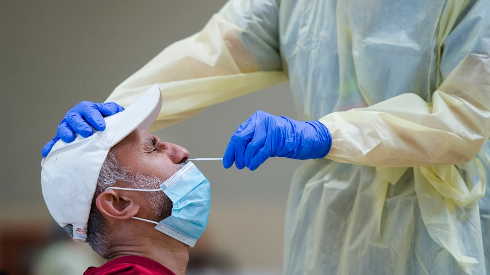 A man gets tested for COVID-19 from a health care worker at a pop-up testing centre at the Islamic Institute of Toronto during the COVID-19 pandemic in Scarborough, Ont., on Friday, May 29, 2020. (THE CANADIAN PRESS/Nathan Denette)