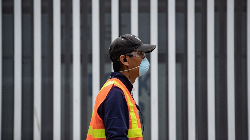 A man wears a face mask and safety glasses in downtown Vancouver, on Saturday, July 11, 2020. (Darryl Dyck / THE CANADIAN PRESS)