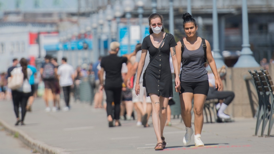 A woman wears a face mask as she walks along the promenade in the Old Port of Montreal, Sunday, August 16, 2020, as the COVID-19 pandemic continues in Canada and around the world. THE CANADIAN PRESS/Graham Hughes