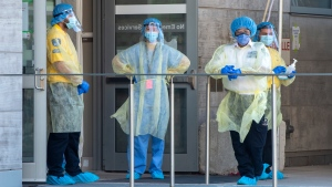 Security guards and a heath-care worker wait for patients at the Women's College Hospital Covid-19 testing centre on Saturday June 6, 2020. THE CANADIAN PRESS/Frank Gunn