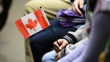 A young new Canadian holds a flag as she takes part in a citizenship ceremony on Parliament Hill in Ottawa on Wednesday, April 17, 2019, to mark the 37th anniversary of the Canadian Charter of Rights and Freedoms. (THE CANADIAN PRESS/Sean Kilpatrick)