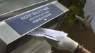 In this July 7, 2020, file photo a woman wearing gloves drops off a mail-in ballot at a drop box in Hackensack, N.J. (AP Photo/Seth Wenig, File)