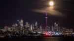 The moon rises behind the skyline in Toronto, Friday January 13, 2017. THE CANADIAN PRESS/Mark Blinch