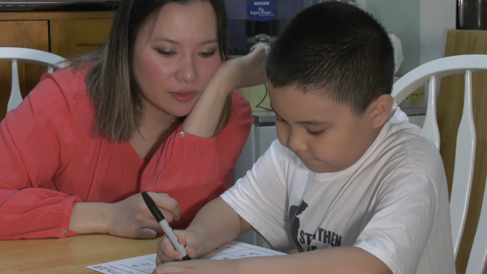 Kaye Banez helps her eight-year-old son, Lazarus, study in their family kitchen on Aug. 20, 2020.