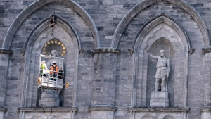 Workers inspect a statue on the facade of the Notre-Dame Basilica in Montreal on Thursday, August, 29, 2019. THE CANADIAN PRESS/Paul Chiasson