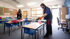 Joshua Lee, right, disinfects tables at Queen's Hill Primary School in Costessey near Norwich, England, Monday, Aug. 24, 2020. Britain's prime minister is asking parents to set aside their fears and send their children back to school next month when the nation's schools fully reopen for the first time since the coronavirus pandemic shut then down more than five months ago. (Joe Giddens/PA via AP)
