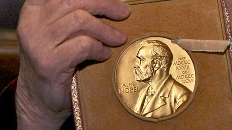 A laureate holds up her Nobel Prize during a ceremony in London, on Wednesday, Jan. 30, 2008. (AP / Matt Dunham)
