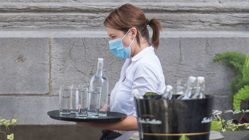 A server wears a face mask as she carries a tray of glasses and water at a restaurant in Montreal, Sunday, July 5, 2020, as the COVID-19 pandemic continues in Canada and around the world. THE CANADIAN PRESS/Graham Hughes
