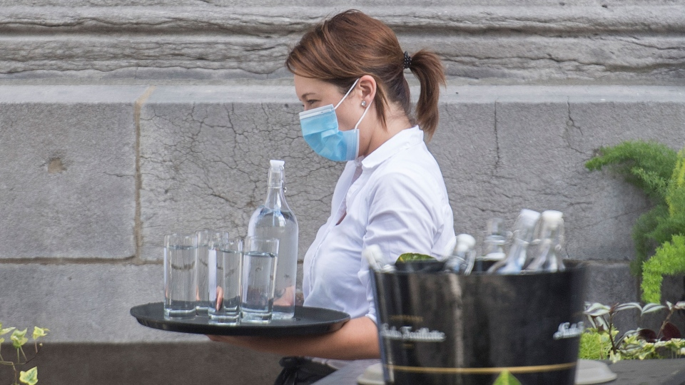 A server wears a face mask as she carries a tray of glasses and water. THE CANADIAN PRESS/Graham Hughes