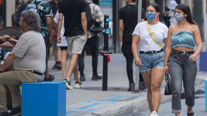 People wear face masks as they walk along a street in Montreal, Saturday, Aug. 22, 2020. THE CANADIAN PRESS/Graham Hughes