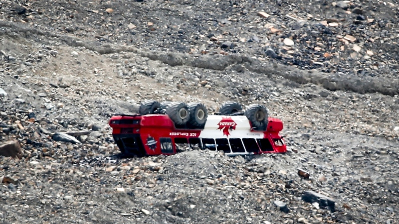 A rolled-over tour bus rests where it fell on the Columbia Icefield near Jasper, Alta., Sunday, July 19, 2020. RCMP say three passengers were killed when the sightseeing bus rolled over at the icefields. THE CANADIAN PRESS/Jeff McIntosh
