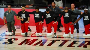 The Toronto Raptors kneel during the national anthem before Game 3 of an NBA basketball first-round playoff series against the Brooklyn Nets, Friday, Aug. 21, 2020, in Lake Buena Vista, Fla. (Kim Klement/Pool Photo via AP)