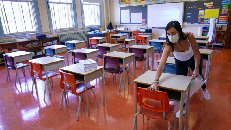 In this file photo, grade one teacher Heidi Dimou arranges the desks in line with physical distancing policy in her class in preparation for the new school year at the Willingdon Elementary School in Montreal, on Wednesday, August 26, 2020. THE CANADIAN PRESS/Paul Chiasson